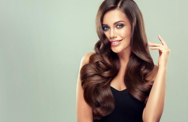 Idealnie wyglądająca młoda kobieta z zębatym uśmiechem na twarzy demonstruje długie, gęste kręcone fryzury i elegancki makijaż idealne loki zadbanych włosów sztuka fryzjerska i pielęgnacja włosów