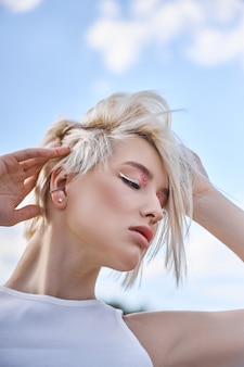 Idealny czerwony manicure do paznokci blond kobieta krótkie włosy. kobieta pozuje latem na łonie natury w słoneczny dzień