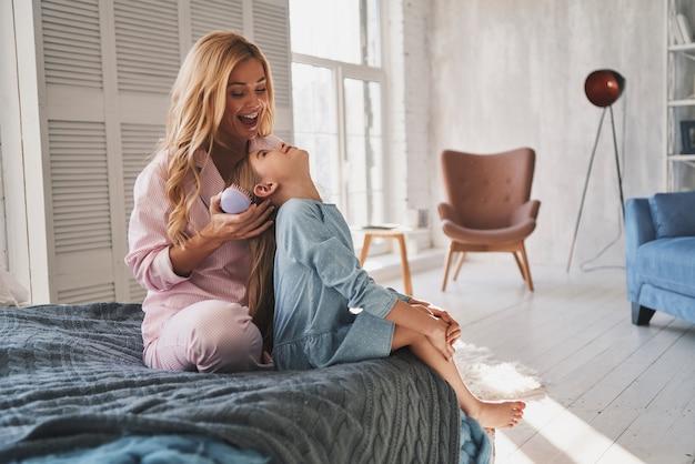 Idealny fryzjer. piękna młoda matka szczotkująca włosy córki siedząc na łóżku w domu