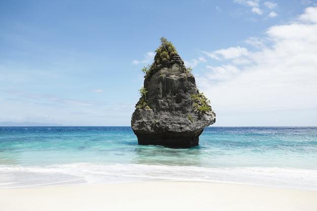 Idealny i spokojny krajobraz morski: błękitne niebo, kamienna wyspa z roślinnością pośrodku oceanu z turkusową wodą.