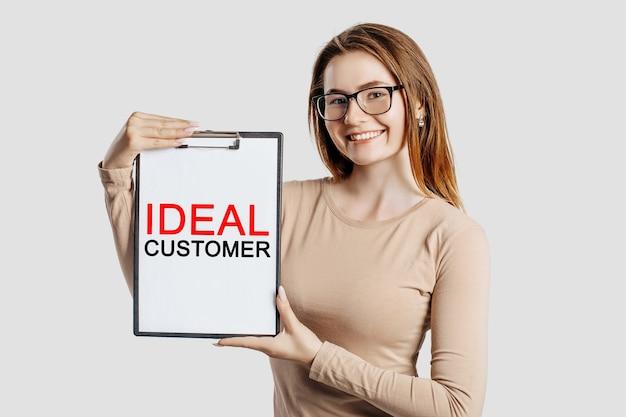 Idealny klient. piękna młoda biznesowa kobieta w okularach posiada schowek