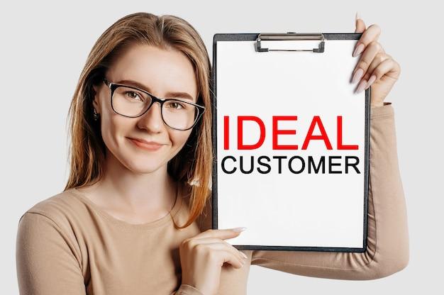 Idealny klient. piękna młoda biznesowa kobieta w okularach trzyma schowek z miejsca na białym tle na szarym tle