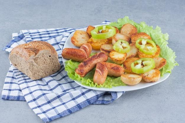 Idealny lunch. kiełbasa smażona i ziemniak na białym talerzu.