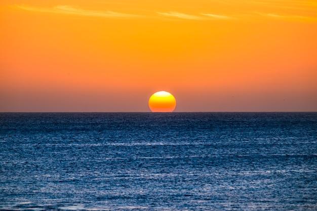 Idealny moment zachodu słońca, gdy słońce dotyka wody na środku oceanu w letnie wakacje na tropikalnej wyspie