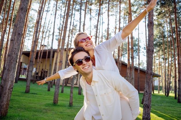Idealny nastrój. pozytywne, radosne małżeństwo bawiące się razem podczas wizyty w letnim domu