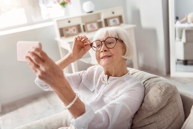 Idealny nastrój. wesoła starsza kobieta siedzi na kanapie i uśmiecha się, dopasowując okulary, podczas robienia selfie w swoim salonie