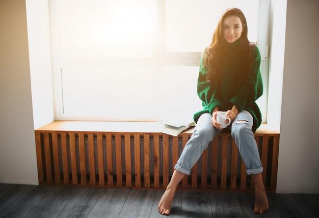 Idealny poranek młoda brunetka kobieta siedzi na parapecie i trzyma w rękach książkę i wypija filiżankę herbaty lub kawy. modelka ubrana w zielony oversize sweter.