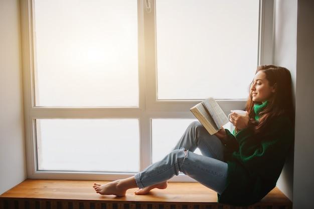 Idealny poranek młoda brunetka kobieta siedzi na parapecie i trzyma w rękach książkę i wypija filiżankę herbaty. modelka ubrana w zielony oversize sweter.
