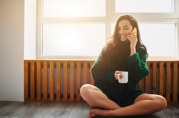 Idealny poranek młoda brunetka kobieta siedzi przy parapecie i trzyma w rękach smartfona. modelka ubrana w zielony sweter.