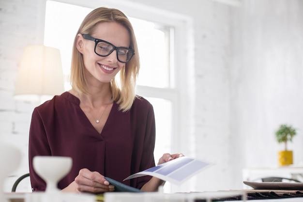 Idealny projekt. niski kąt atrakcyjnej projektantki w okularach i wybierającej tapicerkę