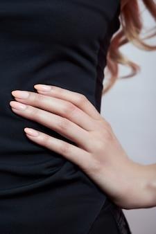 Idealny różowy manicure na kobiecych palcach.