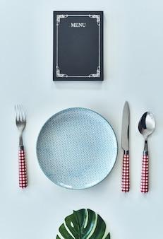 Idealny serwis. ujęcie pod wysokim kątem pustego talerza, widelca, łyżki, noża zamkniętego menu leżącego naprzeciw