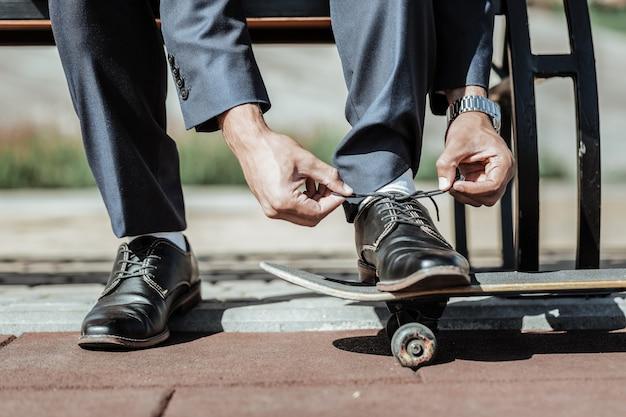 Idealny styl. zbliżenie na delikatne męskie dłonie wiążące sznurówki i przygotowanie do jazdy na deskorolce