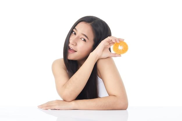 Idealny świeży portret skóry młodej dziewczyny piękne azjatyckie z pomarańczy w ręku na białym tle