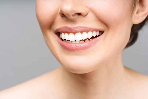 Idealny zdrowy uśmiech zębów młodej kobiety symbolizuje obraz pacjenta wybielający zęby kliniki stomatologicznej