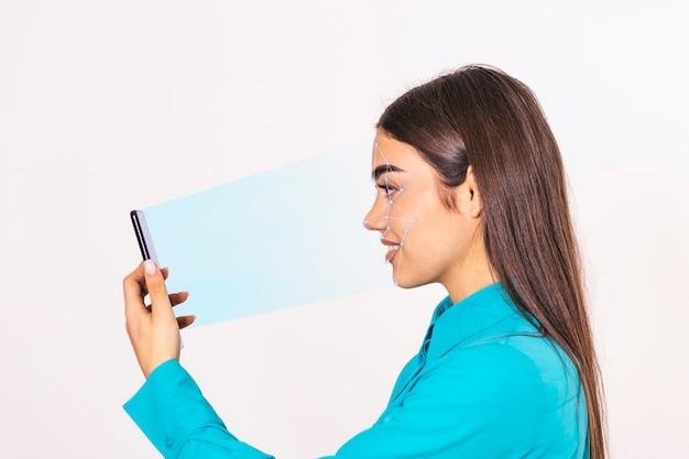 Identyfikacja biometryczna. młoda piękna kobieta skanuje twarz z systemem rozpoznawania twarzy na smartfonie.