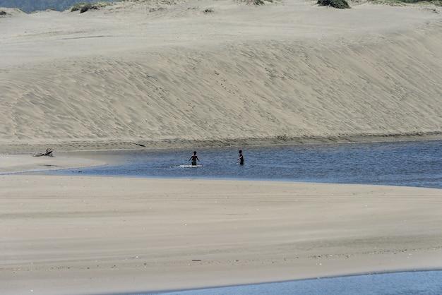 Idylliczna piaszczysta plaża z ludźmi pływającymi w wodzie
