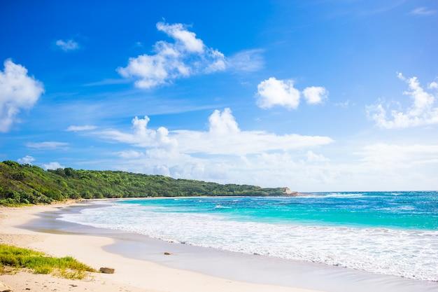 Idylliczna tropikalna plaża na karaibach z białym piaskiem, turkusową oceaniczną wodą i niebieskim niebem