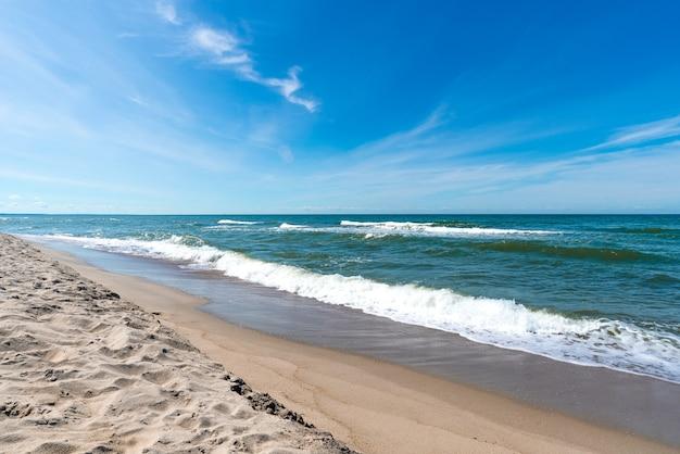 Idylliczna tropikalna plaża z turkusowymi wodami i białym piaskiem w pogodny, słoneczny dzień