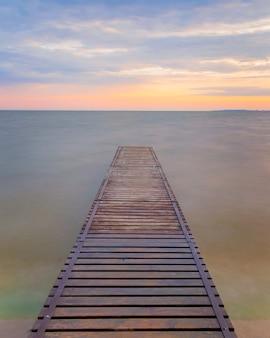 Idylliczny kret (molo) na jeziorze o wschodzie słońca
