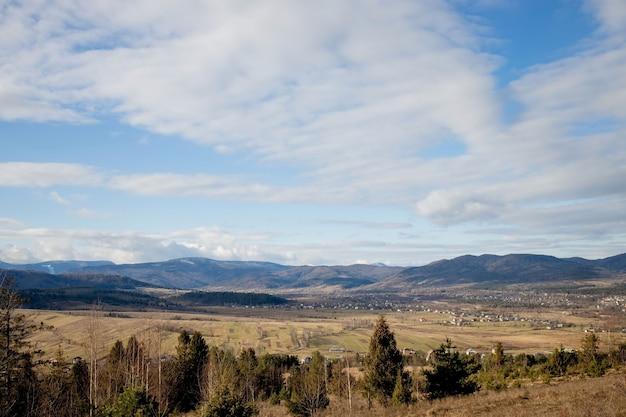 Idylliczny wiejski widok na łagodnie toczące się patchworkowe pola uprawne i wioski z ładnymi, zalesionymi granicami, w pięknym otoczeniu.