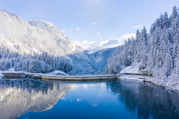 Idylliczny zimowy krajobraz pokrytych śniegiem gór i kryształowego jeziora w szwajcarii
