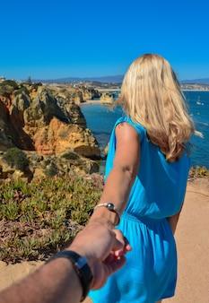 Idź tam za mną. blondynka w niebieskiej sukience trzyma mężczyznę za rękę i wskazuje piękne miejsce na relaks