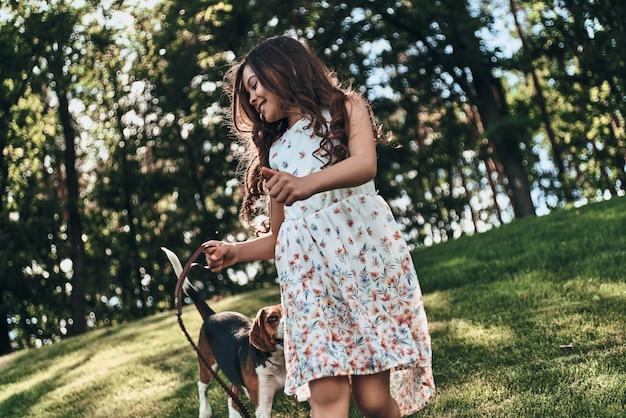 Idziesz? śliczna mała dziewczynka bawi się z psem i uśmiecha się podczas spaceru na świeżym powietrzu