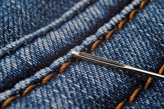 Igła do szycia leży na szwie niebieskiego dżinsu. zbliżenie.