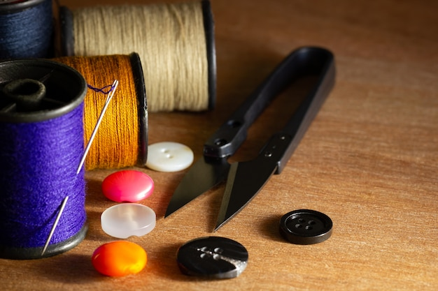 Igła i nici na plastikowym guziku i nożyczki do cięcia nici na drewnianym stole. zamknij i skopiuj miejsce na tekst. koncepcja krawca lub projektanta.