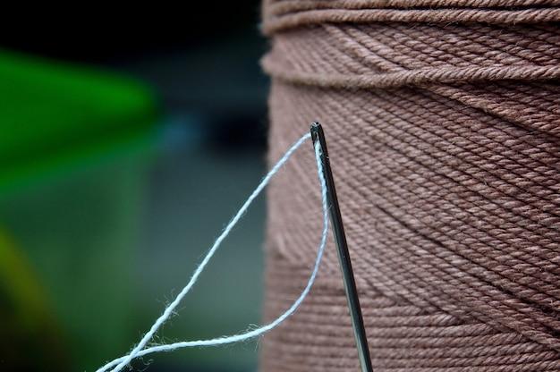 Igła z włożoną w nią nitką na tle dużej szpulki nici