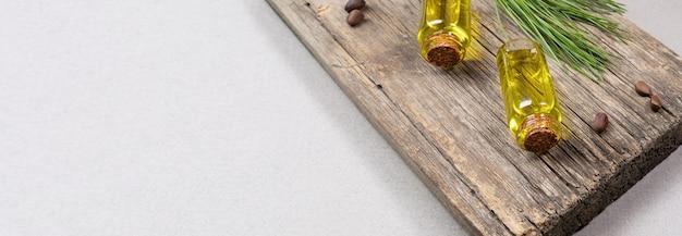 Iglaste spa aromaterapia i baner produktów spa z małych szklanych butelek olejku cedrowego na starej desce z gałązką cedrową i orzechami na szarym tle. skopiuj miejsce na tekst.
