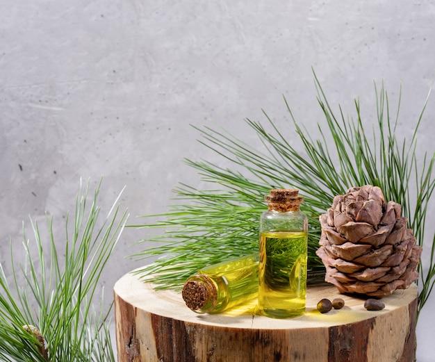 Iglaste spa aromaterapia i produkty spa: małe szklane butelki olejku cedrowego na okrągłym drewnianym pniu z gałęziami cedru, stożkiem, orzechami na szarym tle. skopiuj miejsce na tekst.