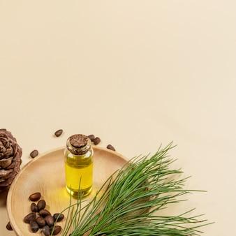 Iglaste spa aromatyczny olejek cedrowy w małej szklanej butelce na drewnianej płycie z gałęzi cedru, stożek, orzechy na beżowym tle z miejsca na kopię. koncepcja aromaterapii i spa. zdjęcie kwadratowe.