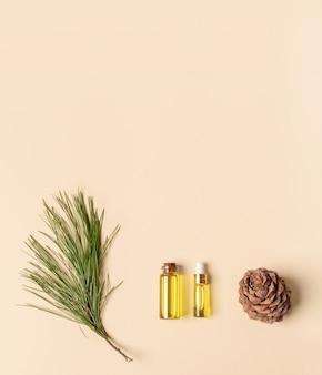 Iglaste spa aromatyczny olejek cedrowy w małych szklanych butelkach, gałąź, stożek na beżowym tle. koncepcja aromaterapii i spa. widok z góry, kopia przestrzeń. orientacja pionowa.
