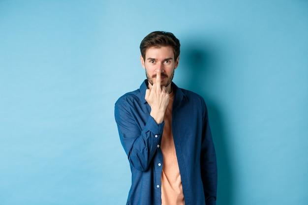 Ignorant i niegrzeczny facet pokazujący środkowy palec i uśmiechnięty, powiedz: pieprzyć cię, stojąc na niebieskim tle.