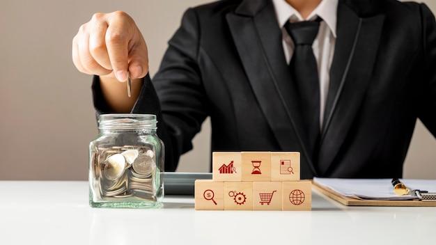 Ikona biznesowa na drewnianym sześcianie i ręka wkładająca monetę do oszczędności butelka pieniądze koncepcja finansów