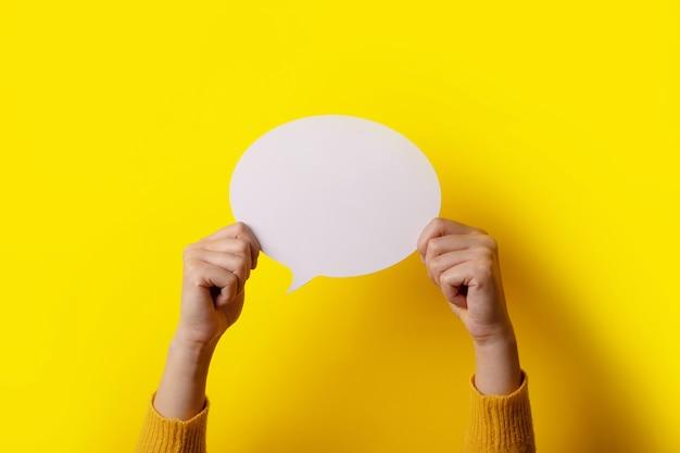Ikona dialogu, pusty dymek w dłoni na żółtym tle, obraz układu