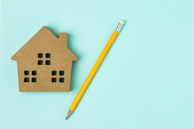 Ikona domu brązowy drewna i ołówek na niebieskim tle