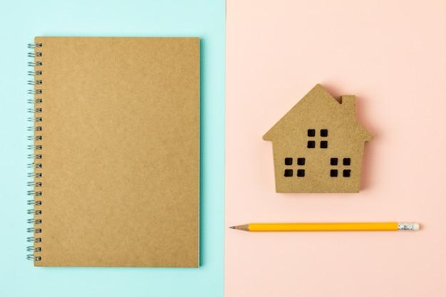 Ikona domu brązowy drewna i pamiętnik na tle niebieski i różowy