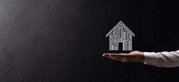 Ikona domu trzymaj rękę. inteligentny dom kontrolowany, inteligentny dom i koncepcja aplikacji automatyki domowej. projekt pcb i osoba z inteligentnym telefonem. innowacyjna technologia internetowa koncepcja sieci.