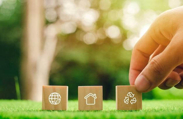 Ikona drewnianego klocka z dotknięciem dłoni z technologią łączącą ręce z ikonami środowiska poprzez połączenie środowiska.