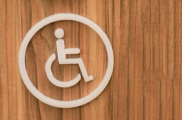 Ikona osoby niepełnosprawnej. śpiewać i symbol osoby niepełnosprawnej na drewnianym.