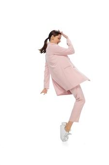 Ikona. szczęśliwa młoda kobieta tańczy w zwykłym ubraniu lub garniturze, przerabiając legendarne ruchy i tańce celebrytów z historii kultury. na białym tle. akcja, ruch, koncepcja sławy. twórczy zawód.