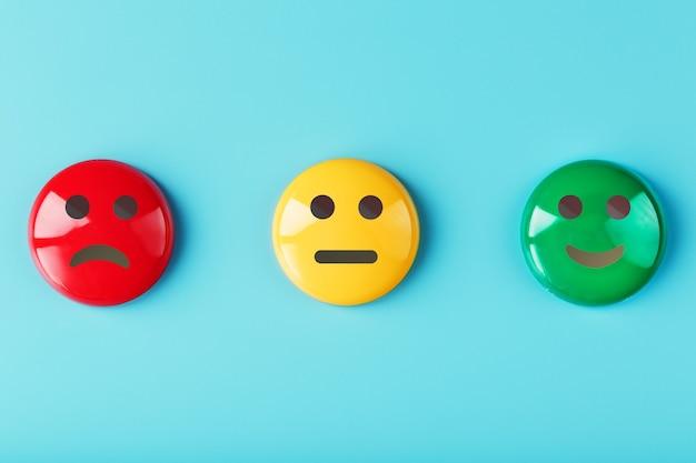 Ikony ankiety satysfakcji emocjonalnej są czerwone, żółte, zielone na niebieskiej powierzchni