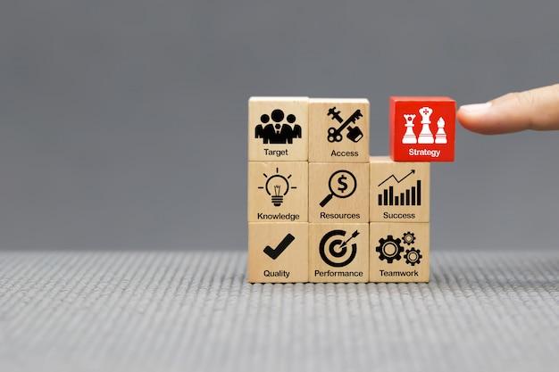 Ikony strategii na drewnianym bloku dla sukcesu, wydajności, zarządzania i rozwoju firmy.