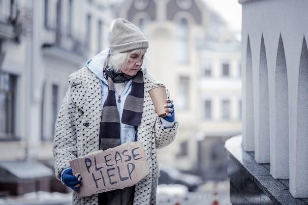 Ile mam, smutna, bezradna kobieta patrzy w kubek, sprawdzając, ile ma pieniędzy