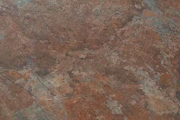 Ilustracja przedstawiająca pomarańczowo-brązową powierzchnię z zadrapaniami i rdzą