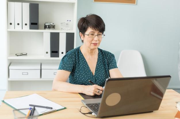 Ilustratorka, projektantka stron internetowych i koncepcja artysty - projektantka graficzna używająca swojego tabletu piórkowego na jasnym tle