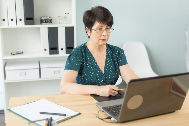 Ilustratorka, projektantka stron internetowych i koncepcja artysty - projektantka graficzna używająca tabletu piórkowego w jasnym biurze.
